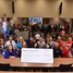 Educators pose for a photo with big check for STEM grants